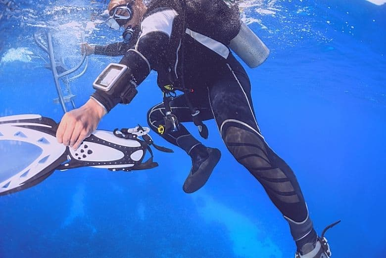 scuba diver taking fins off